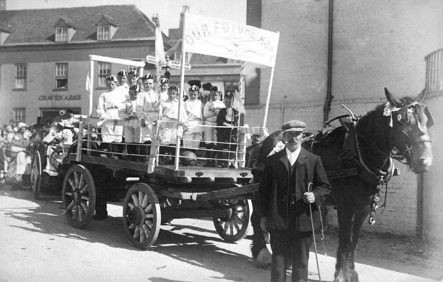 [Southam May Day], horse drawn float containing a group of small boys with the banner 'Our Future Hope', with a crowd and another float outside the Craven Arms, High Street; the driver of the first float is standing in the foreground.  1908 |  IMAGE LOCATION: (Warwickshire County Record Office)