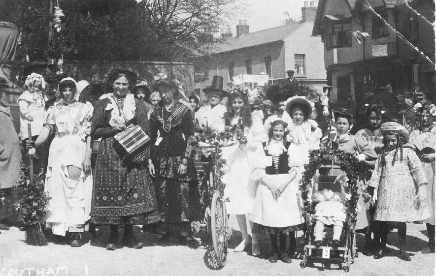 May Day group of children and adults with decorated prams, bicycles and wearing fancy dress.  1900s.    . |  IMAGE LOCATION: (Warwickshire County Record Office)