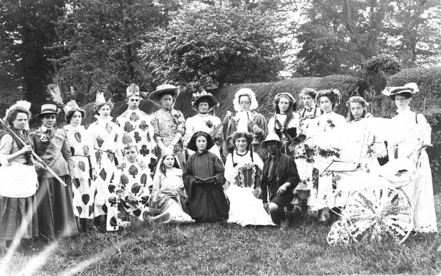 Group in fancy dress with decorated pram in the garden of the Abbey. Believed to be May Day, Southam. 1908 |  IMAGE LOCATION: (Warwickshire County Record Office) IMAGE DATE: (c.1908)