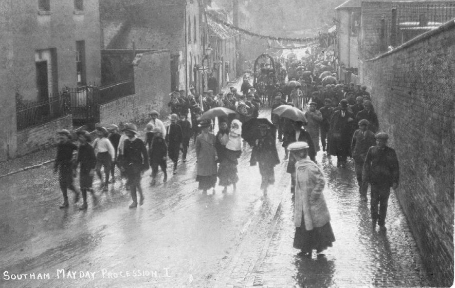 Southam May Day Procession coming up Warwick Street; in pouring rain, with band, decorated carts, umbrellas etc.  1900s |  IMAGE LOCATION: (Warwickshire County Record Office) IMAGE DATE: (c.1907)