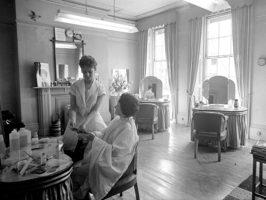 Interior view of the salon of Allen Steel, Hairdresser in The Parade, Leamington Spa, showing an employee hairdresser with client.  1960 |  IMAGE LOCATION: (Warwickshire County Record Office)