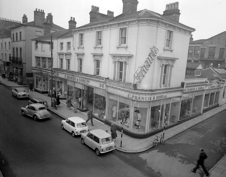 Exterior of front and one side of  E. Francis & Sons Ltd,  on corner of The Parade and Regent Street, Leamington Spa. Pedestrians and motor cars in street.  1961 |  IMAGE LOCATION: (Warwickshire County Record Office)