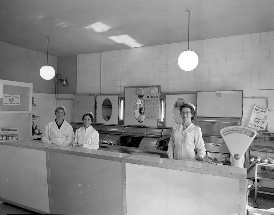 Interior of Mrs. Ramsey's Fish and Chip Shop in Crown Way, Lillington, Leamington Spa, showing staff behind counter, fryers etc.  1960s |  IMAGE LOCATION: (Warwickshire County Record Office)