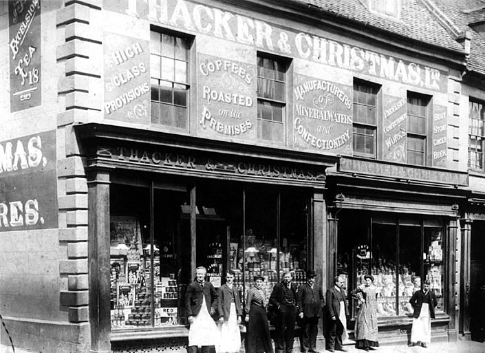 Exterior of Thacker & Christmas, grocers and tea dealers in High Street, Warwick. Standing in front of the shop are a group of employees.  1900s |  IMAGE LOCATION: (Warwickshire Museums. Photographic Collections.)