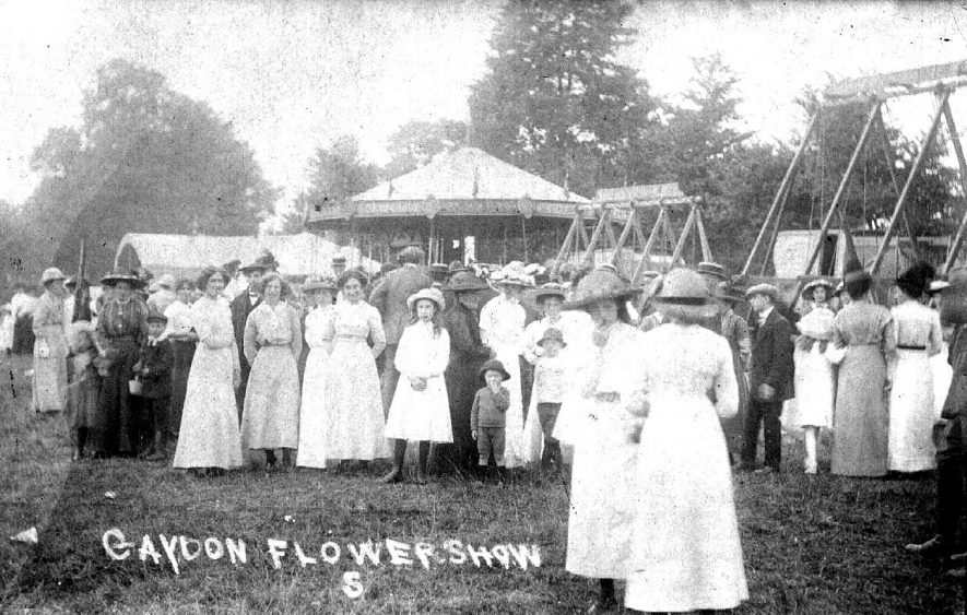 A crowd at a flower show in Gaydon, a fun fair in the background.  1900 |  IMAGE LOCATION: (Warwickshire County Record Office)
