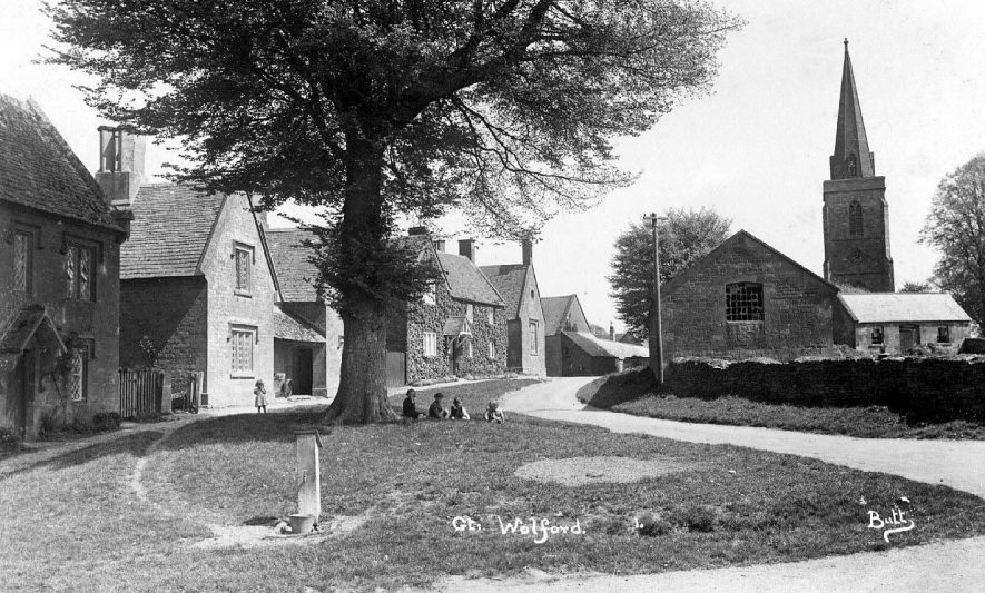 Village scene with cottages round a green and the church in the background.  1920s |  IMAGE LOCATION: (Warwickshire County Record Office)