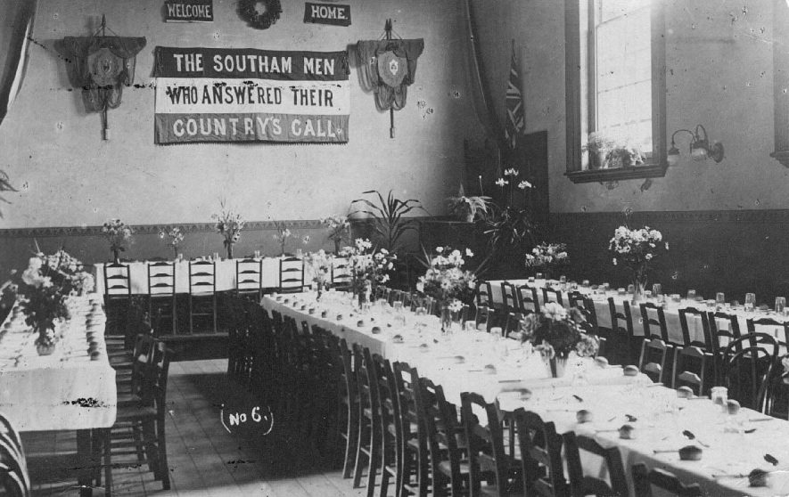 Interior of the Court House, showing tables set for dinner and banners on the wall saying 'Welcome Home, The Southam Men Who Answered Their, Country's Call'.  1918 |  IMAGE LOCATION: (Warwickshire County Record Office)