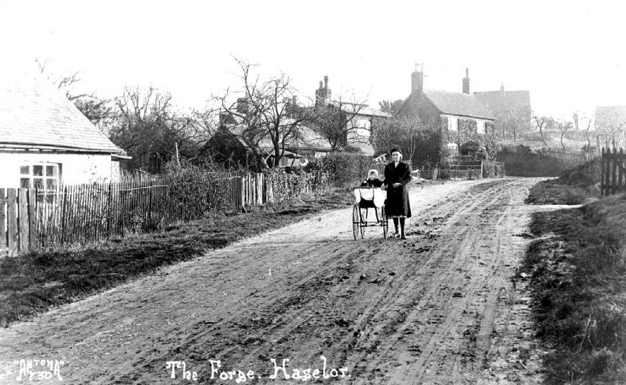 The Forge at Haselor. Woman and perambulator standing in the muddy road.  1910s |  IMAGE LOCATION: (Warwickshire County Record Office)