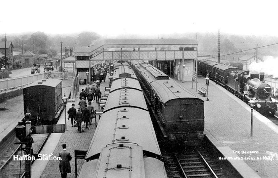 Hatton railway station, footbridge, passenger trains and passengers on platform.  1900s    IMAGE LOCATION: (Warwickshire County Record Office)