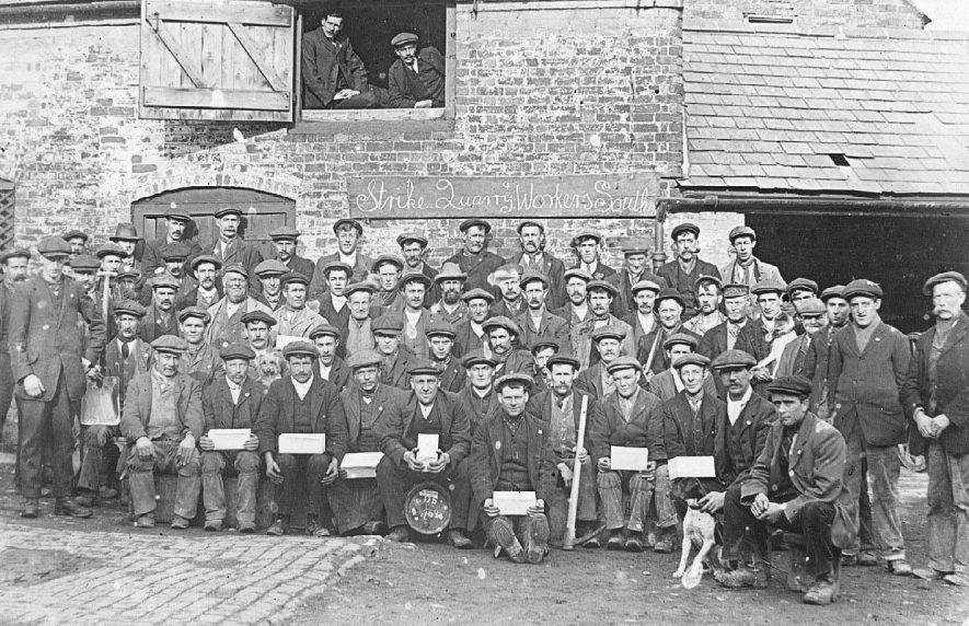 'Strike Quarry Workers, Southam'; the photograph, taken at the Bull Inn, shows the strikers with collecting boxes, picks, shovels and dogs. (looking out from the left are G. Morris of Coventry, the Workers Union strike organiser, and Mr. F.G. Berry of Southam, fourth from the right on the front row is Walter Beach).  1912 |  IMAGE LOCATION: (Warwickshire County Record Office) PEOPLE IN PHOTO: Morris, G, Morris as a surname, Berry, F G, Berry as a surname, Beach, Walter, Beach as a surname