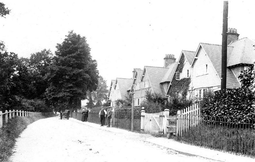 Houses in New Road, Henley-in-Arden with people standing outside. Unidentified small horse drawn wagon in the background.  1900s |  IMAGE LOCATION: (Warwickshire County Record Office)