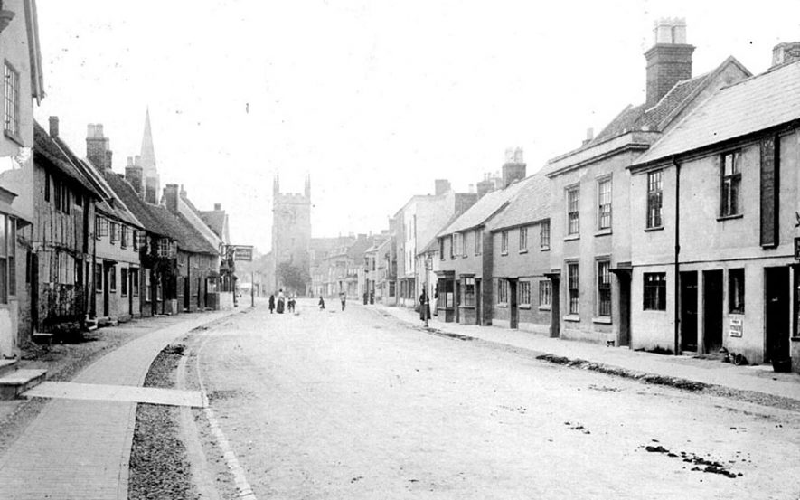 High Street in Henley in Arden with church tower and church spire in the background.  1900s |  IMAGE LOCATION: (Warwickshire County Record Office)