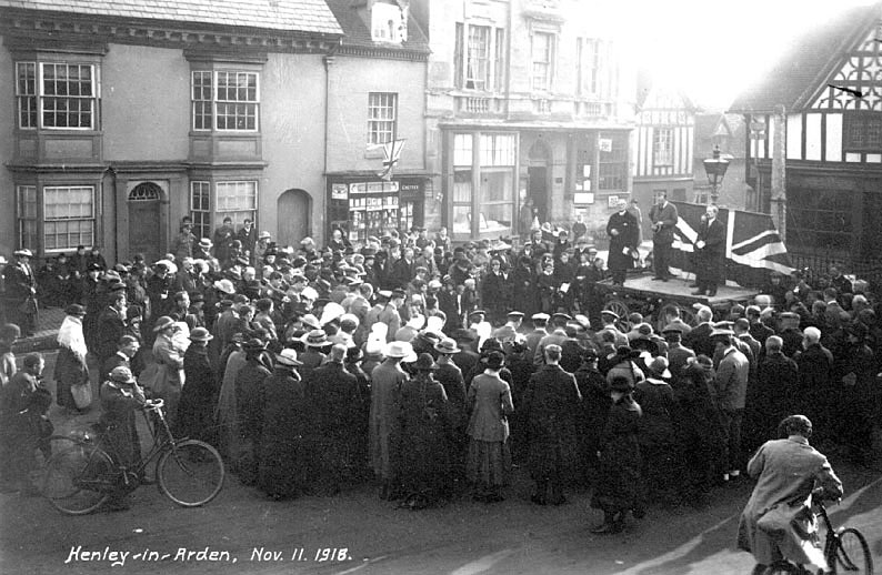 Crowd of people in Henley-in-Arden celebrating Armistice Day.  November 11th 1918 [The indoor service planned for 11th Nov. was called off because of the 'Spanish' influenza. Instead, an outdoor meeting was held on 12th Nov. in the Market Place. Dr Nelson (the High Bailiff) made a short speech; also on the platform were the Revd. L.G.Schofield and Mr T.R.Perkins.] |  IMAGE LOCATION: (Warwickshire County Record Office)