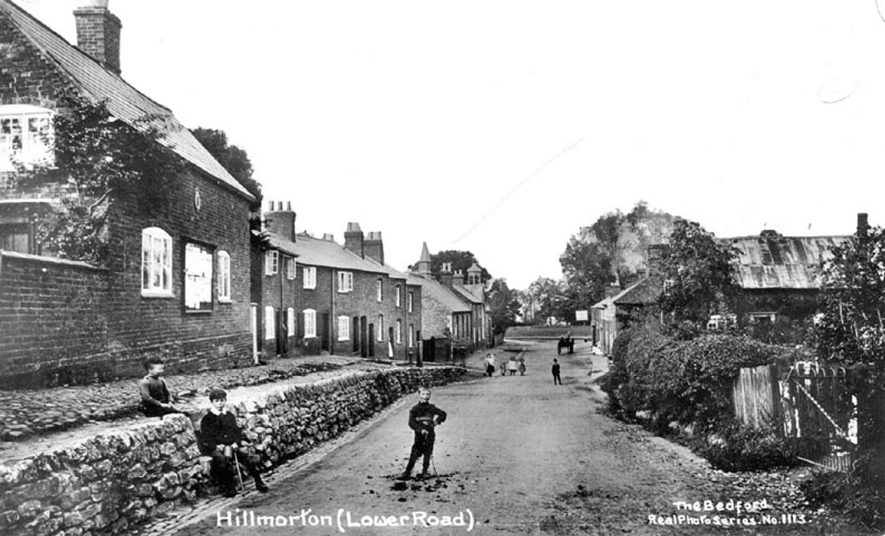 Lower Road, Hillmorton with children standing in road.  1920s [The cottages on the left in the middle distance still exist, as does the Stag and Pheasant pub, who's sign can be seen in the right centre. The school is clearly visible across the road from the pub.]  [This road is actually called Lower Street. The lowest of the roads serving the community in that area (later development joined Lower Hillmorton and Hillmorton together.] |  IMAGE LOCATION: (Warwickshire County Record Office)