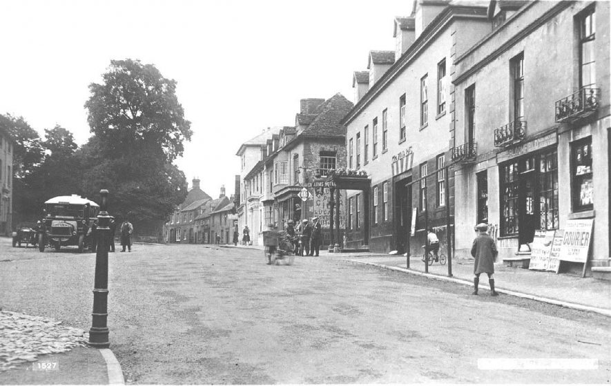 View north along Market Hill; shows the 'Craven Arms' Hotel and a newsagents with a <i>Leamington Courier</i> hoarding. Several adults and children in the street, including two boys with bicycles and three men grouped around a motor bike; a Midland Motor Service bus is parked by the side of the road.  1920s |  IMAGE LOCATION: (Warwickshire County Record Office)