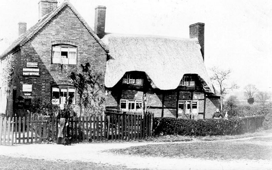 Post office and adjoining thatched cottage, Hunningham. Two women, one by gate and one with dog.  1900s    IMAGE LOCATION: (Warwickshire County Record Office)