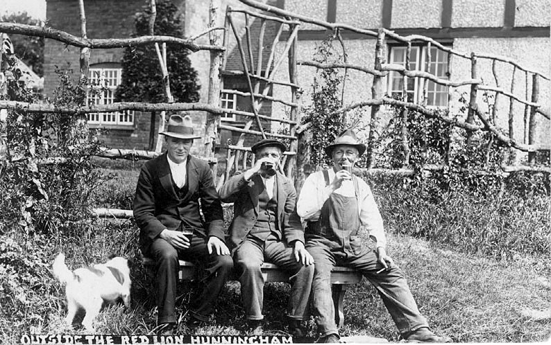 Three men drinking outside The Red Lion, Hunningham. Terrier dog.  1930s |  IMAGE LOCATION: (Warwickshire County Record Office)