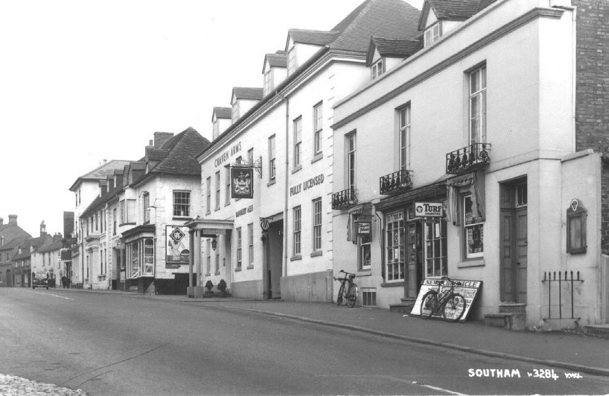Market Hill, view of the Craven Arms Inn and a newsagents owned by  A.J. Masters; two bicycles outside the newsagents.  1950s |  IMAGE LOCATION: (Warwickshire County Record Office)