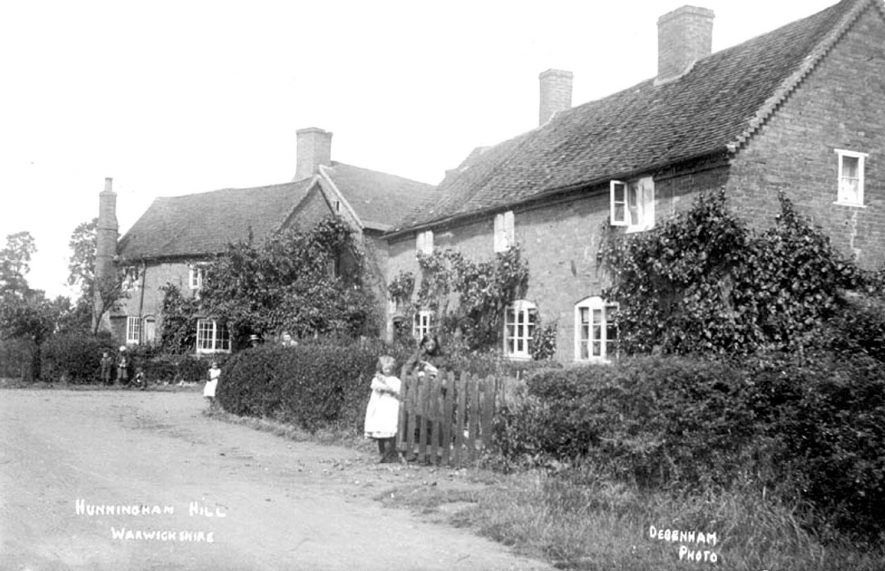Brick terraced cottages and front gardens, with children at the gates, Hunningham Hill.  1900s    IMAGE LOCATION: (Warwickshire County Record Office)