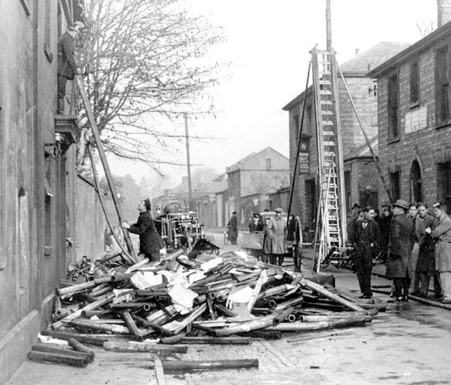 Firemen and public at scene of recent fire at glove factory in Upper Grove Street, showing fire engine and ladder, Leamington Spa.  1930s    IMAGE LOCATION: (Warwickshire County Record Office)