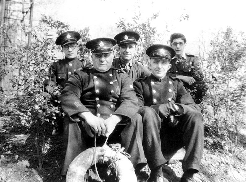 A group of five auxiliary firemen sitting outside Adelaide Road HQ, Leamington Spa. L-R:  Ron Wood, Vic Godfrey, Charlie Rogers, Louis Gallagher, Rama Khatamal.  1940s    IMAGE LOCATION: (Warwickshire County Record Office) PEOPLE IN PHOTO: Wood, Ron, Wood as a surname, Rogers, Charlie, Rogers as a surname, Khatamal, Rama, Khatamal as a surname, Godfrey, Vic, Godfrey as a surname, Gallagher, Louis, Gallagher as a surname