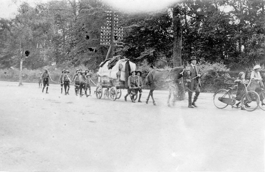 Arrival on foot of Arley Council School boy scouts (or venturers) with home-made wagon and tents and a pit pony, after camping the night at Stoneleigh Park, at Warwick Castle. Woman and girl with bicycles.  Whitsun.  1920 |  IMAGE LOCATION: (Warwickshire County Record Office)