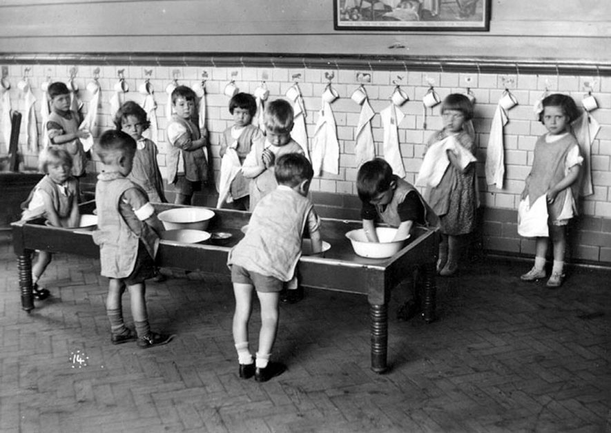 George Street Infants' School nursery class, Bedworth. Hand washing in bowls in old sand tray. 1930s. |  IMAGE LOCATION: (Warwickshire County Record Office)