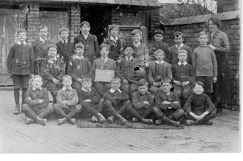 Group photograph of school boys with teacher. Board reads