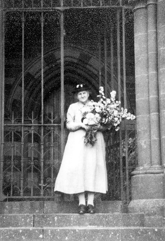 Alice Hyde on the steps of Winderton Church at Harvest Festival. 1930s |  IMAGE LOCATION: (Warwickshire County Record Office) PEOPLE IN PHOTO: Hyde, Alice, Hyde as a surname
