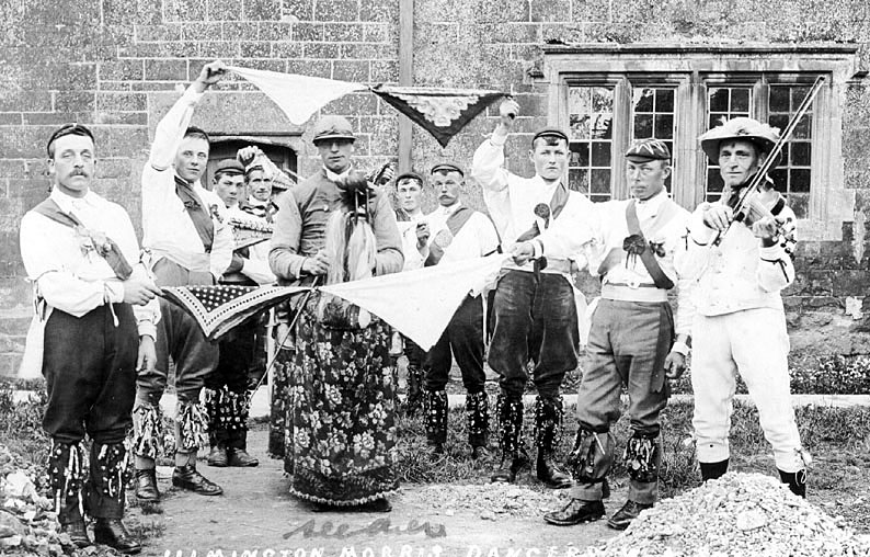 Group of Morris Dancers with handkerchiefs, Ilmington.  1900s  [The Morris Men are dancing 'The Maid of The Mill'unique to the Ilmington morris dance tradition as a linked handkerchief dance.The musician is Sam Bennett, fiddle player who died in 1951 aged 85 years. The dance is still danced to this day by the current Ilmington Morris dancers, who usually dance around the local villages on a Wednesday evening from May to August]     IMAGE LOCATION: (Warwickshire County Record Office)