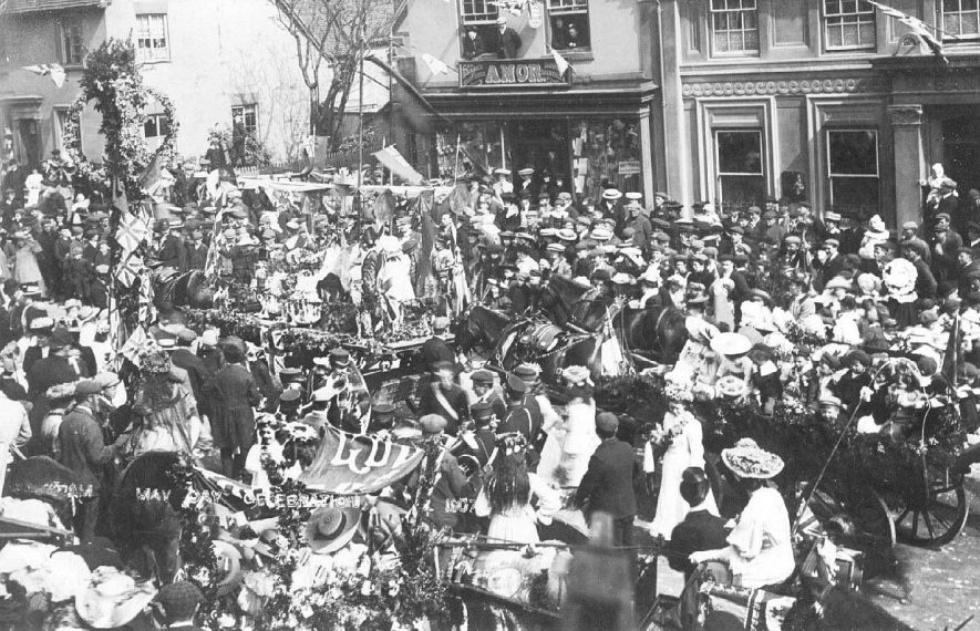 May Day celebrations on Market Hill. A  large crowd watching a procession of horse drawn floats.  Photo: H. Elkington, Broadwell, Rugby.  1907 |  IMAGE LOCATION: (Warwickshire County Record Office)