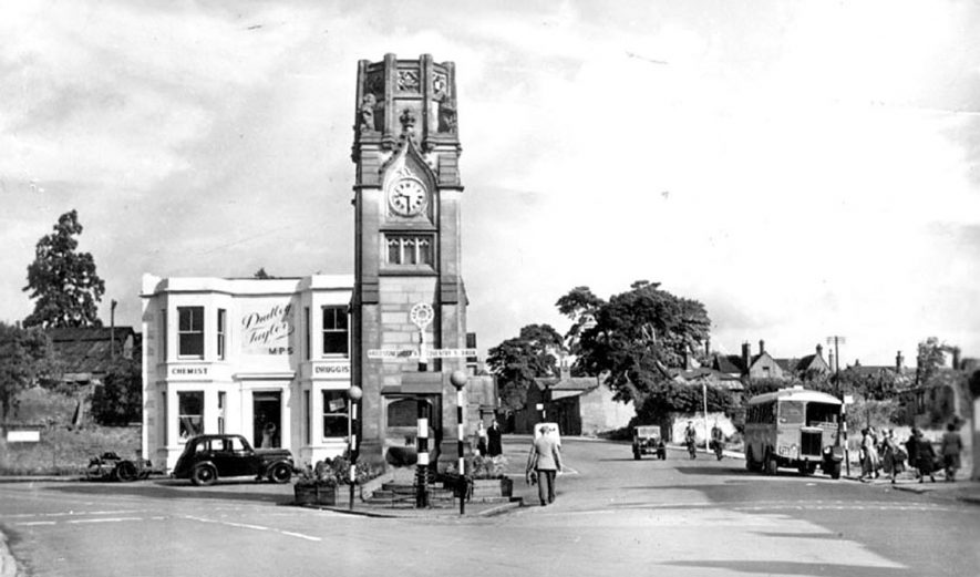 The Clocktower and Dudley Taylor's chemist shop in The Square, Kenilworth.  1950s |  IMAGE LOCATION: (Warwickshire County Record Office)