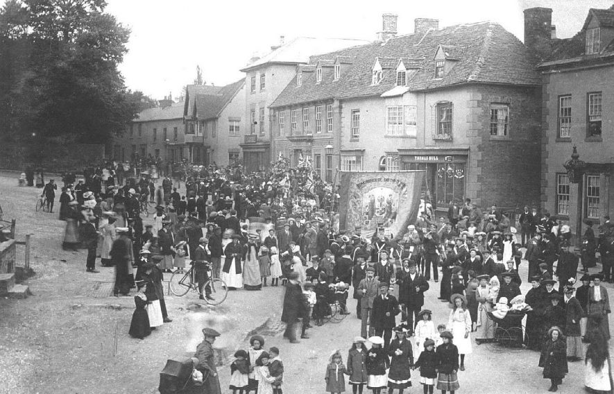 Friendly Societies Parade, with banner of Edmondscote District, with officers and a band, heading south along Market Hill; watched by a crowd, with children, prams etc.  31st May 1908 |  IMAGE LOCATION: (Warwickshire County Record Office)