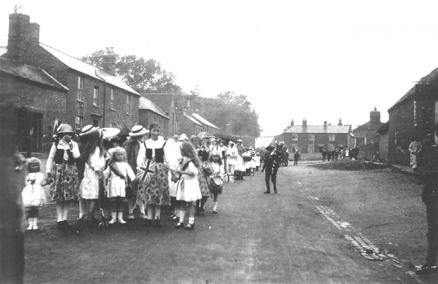 May Day Procession of adults and children with flags, some in fancy dress, heading south along Coventry Street.  1920s |  IMAGE LOCATION: (Warwickshire County Record Office)