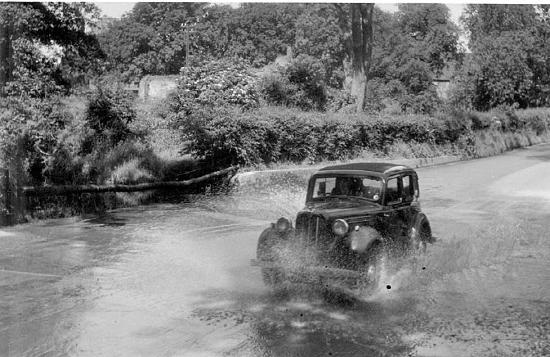 A motor car going through the ford near Kenilworth Castle.  1950s |  IMAGE LOCATION: (Warwickshire County Record Office)