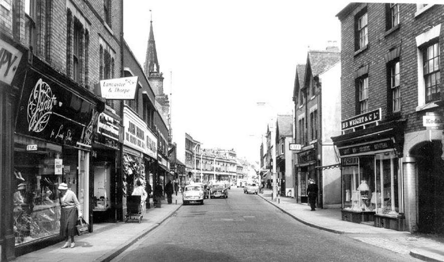 Abbey Street, Nuneaton, with shops on either side.  1960s |  IMAGE LOCATION: (Warwickshire County Record Office)