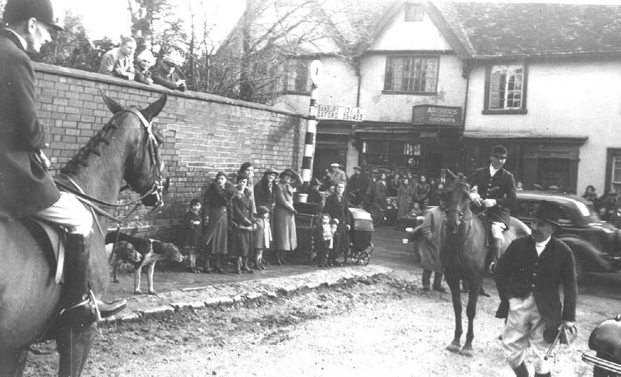 Meet of Warwickshire Hounds at the north end of Market Hill, opposite Archer's chemist; shows three members of the hunt, two on horseback, being watched by a small crowd.  c.1938 |  IMAGE LOCATION: (Warwickshire County Record Office)
