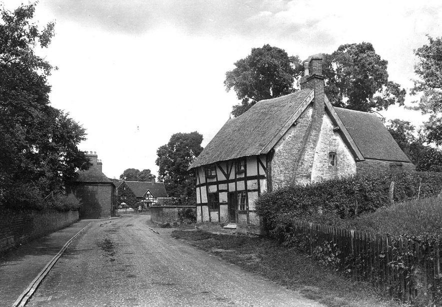Part of Whitnash village, showing thatched and timbered cottage and timbered house in distance.  1922 |  IMAGE LOCATION: (Warwickshire County Record Office)