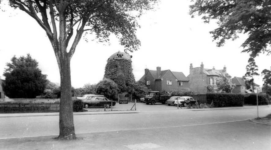 Ivy covered remains of old wind mill, and semi detached houses. Leamington Spa.  1960s |  IMAGE LOCATION: (Warwickshire County Record Office)