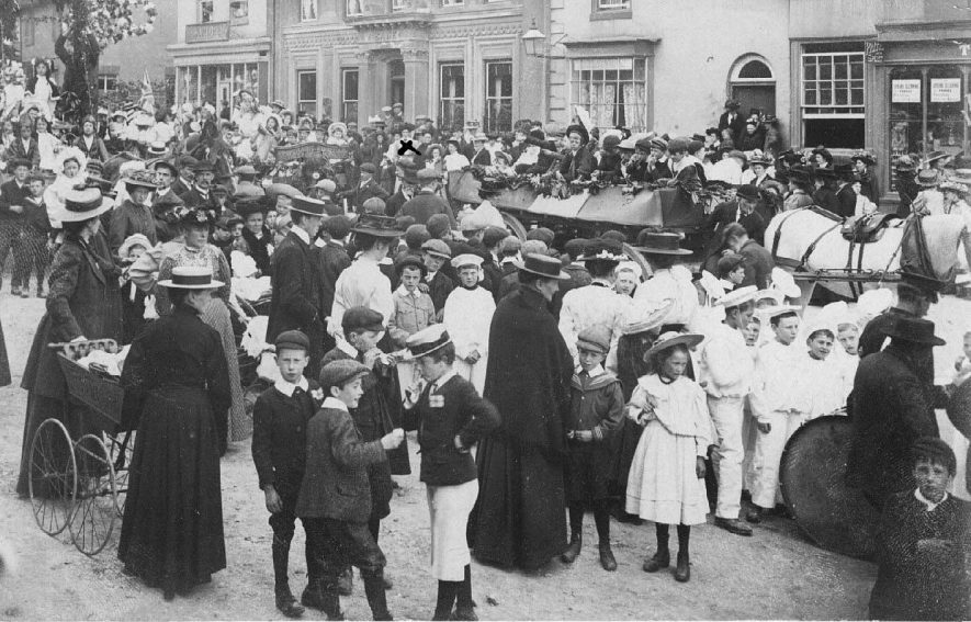 May Day parade through Market Hill; showing decorated horse drawn carts, including one from the Co-operative Industrial Society Ltd. of Southam, carrying children, some in fancy dress. Large crowd, including many children, watching the event, also two women with a pram in the foreground.  1900s |  IMAGE LOCATION: (Warwickshire County Record Office)
