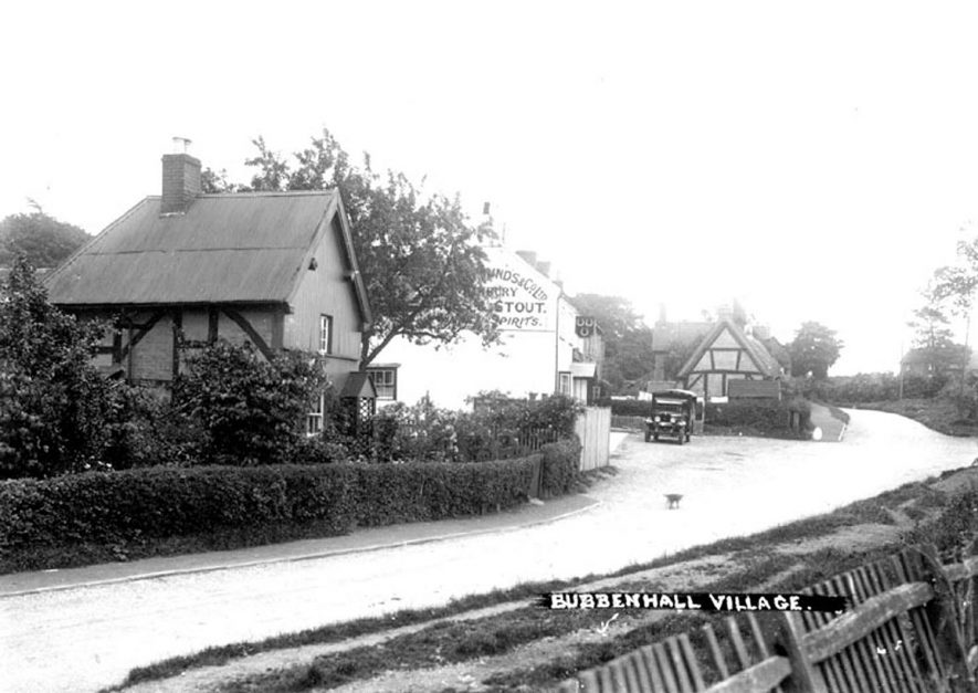 Bubbenhall village scene: timbered cottages, public house with Three Horseshoes sign. Motor vehicle.  1930s |  IMAGE LOCATION: (Warwickshire County Record Office)