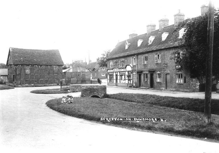 Terraced houses and general stores at side of brook in Stretton on Dunsmore. Timbered barn. Children in grass by small bridge.  1930s |  IMAGE LOCATION: (Warwickshire County Record Office)