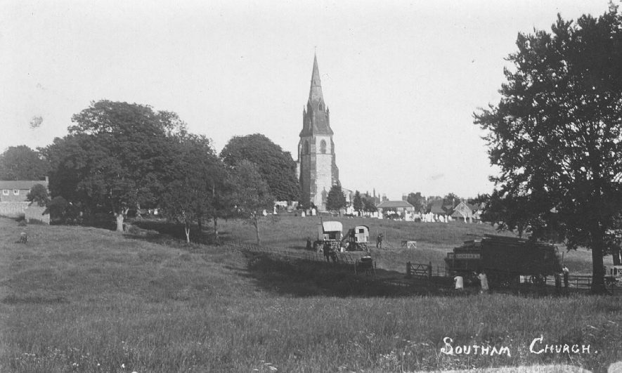 View from the east to St James' Church and Southam; fields in the foreground with caravans and agricultural machinery.  1900s |  IMAGE LOCATION: (Warwickshire County Record Office)