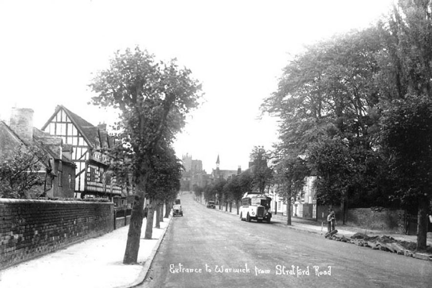 Stratford Road leading to Westgate, Warwick. Timbered inn, motor bus and parked cars. Labourer mending road.  1930s |  IMAGE LOCATION: (Warwickshire County Record Office)