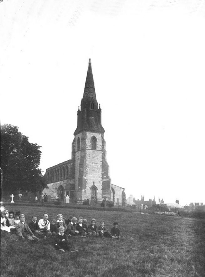 Southam Church. Children sitting on grass.  1900s |  IMAGE LOCATION: (Warwickshire County Record Office)