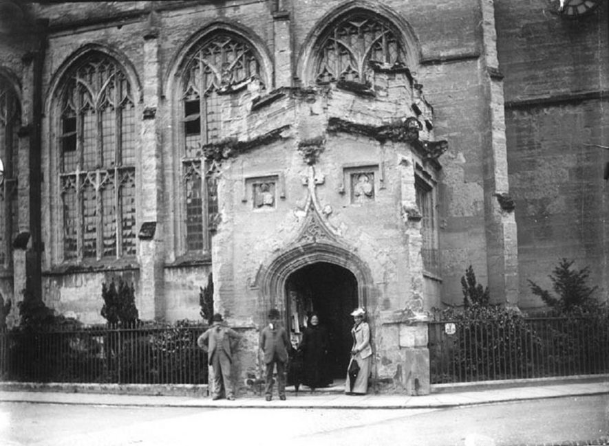 Guild Chapel, doorway and windows, two men, two women standing by porch, Stratford upon Avon.  1900s |  IMAGE LOCATION: (Warwickshire County Record Office)