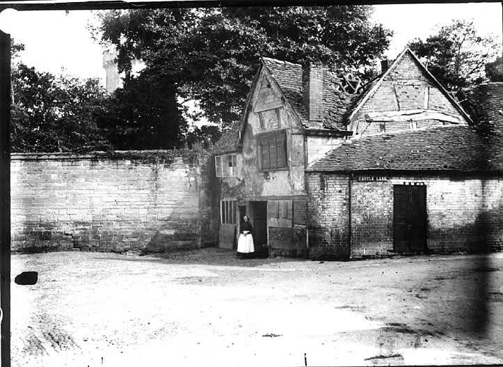 Old, derelict cottage with a lady standing in front, Castle Lane, Warwick.  1900s |  IMAGE LOCATION: (Warwickshire County Record Office)