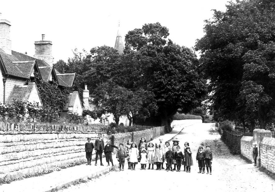 Group of children, possibly school children, standing on Church Bank, outside Temple Grafton School. The church spire can be seen in the background.  1900s |  IMAGE LOCATION: (Warwickshire County Record Office)