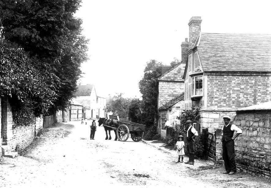 Horse and cart in village street with men and children standing by.  1900s |  IMAGE LOCATION: (Warwickshire County Record Office)