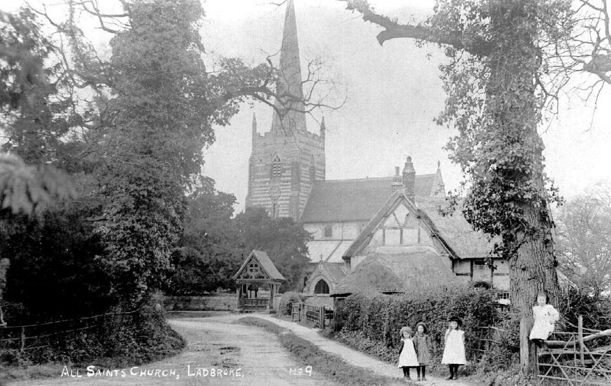 All Saints Church, Ladbroke showing lych gate, half-timbered house and three children standing in the road.  1910s |  IMAGE LOCATION: (Warwickshire County Record Office)